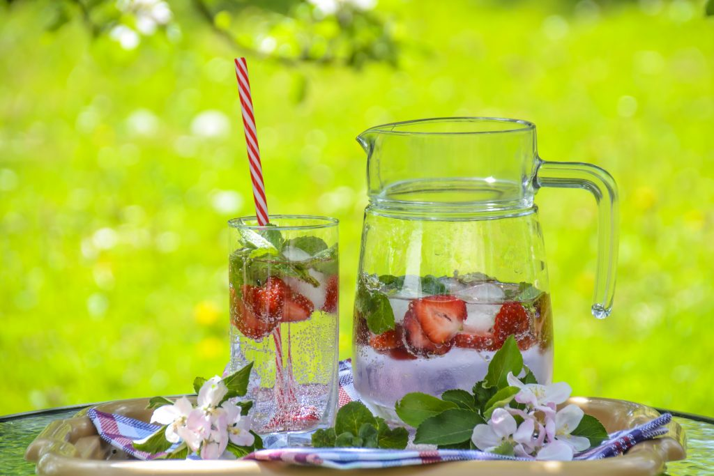 Delicious ice drink with strawberries, mint and ice on the background of of solar garden